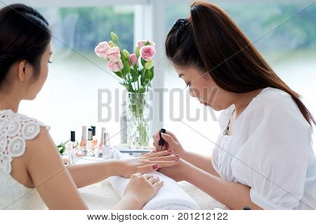 Vietnamese manicurist painting nails of client with deep pink color