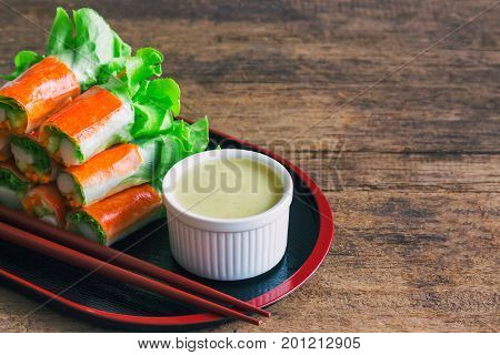 Fresh spring rolls with fresh vegetable and crab stick served with wasabi mixed salad cream dipping sauce. Rolls salad or fresh spring roll in Japanese style healthy tasty food for appetizer or meal.  Fresh spring rolls in fusion food style