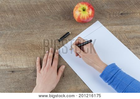 Woman hands holding fountain pen and blank piece of paper on wooden table with red apple