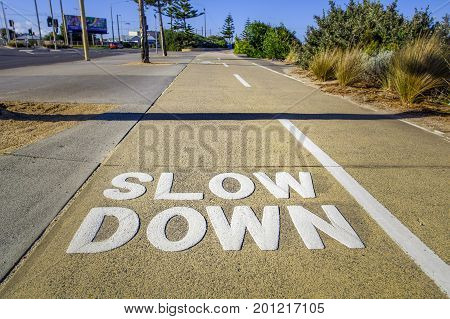 Big Slow Down sign on the footpath closeup