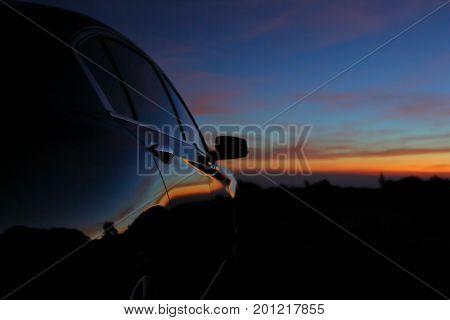 Black Vehicle Car With Reflection Of Landscape Sunset Dramatic Dusk Sky