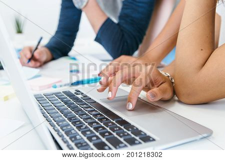 Close-up shot of anonymous woman using laptop at table with coworkers in process of communication.