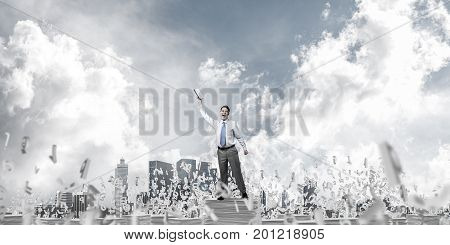 Businessman keeping hand with book up while standing among flying letters with cloudly sky on background. Mixed media.