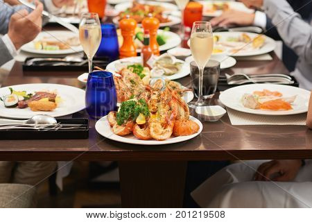 Plate with seafood and glass with champagne at dinner table