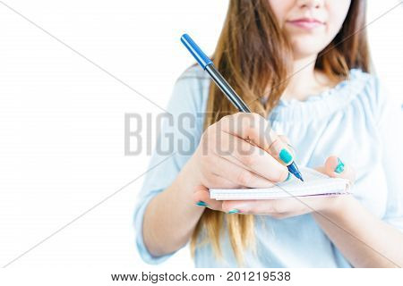 Crop girl holding notepad and writing with pen on white background.