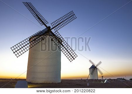 Illuminaed traditional windmills at rising Campo de Criptana Spain poster