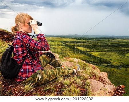 The girl sits on the mountain and looks into the distance with binoculars. At the bottom are green fields.