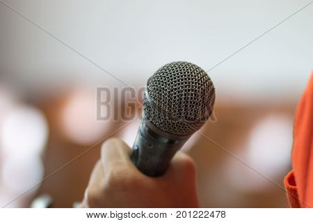 blurred of hands holding businesspeople speech and speaking with microphones in seminar talking conference hall light with microphones and keynote. Speech is vocalized form of communication humans.