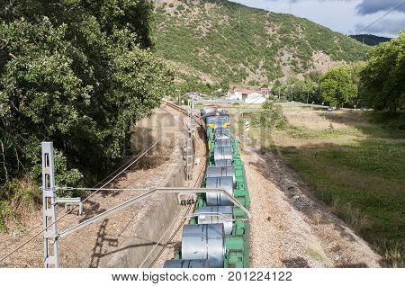 Freight train on an Iberian gauge railway track between Leon and Gijon on its way through La Pola de Gordon, Leon Province, Spain, on August 12 2014
