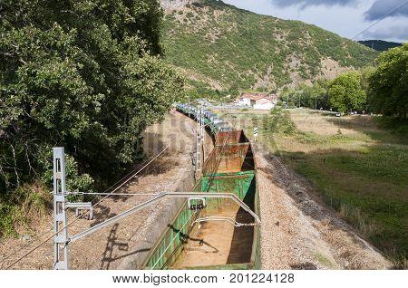 Freight train on an Iberian gauge railway track between Leon and Gijon on its way through La Pola de Gordon, Leon Province Spain, on August 12 2014