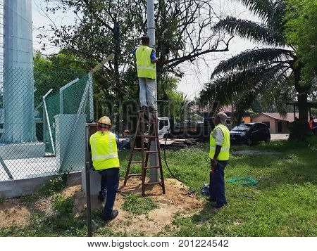 IPOH MALAYSIA - AUGUST 24 2017 - Three electricians are installing three phase overhead four core power cable on concrete spun pole.