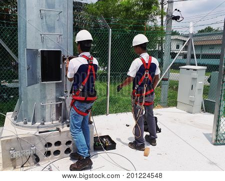 Ipoh, Malaysia – August 24, 2017 – Two Riggers With Safety Harness Installing Fall Arrestor System O