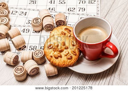 Board Game Lotto On White Desk. Wooden Lotto Barrels And Game Cards With Cup Of Coffee And Cookies O