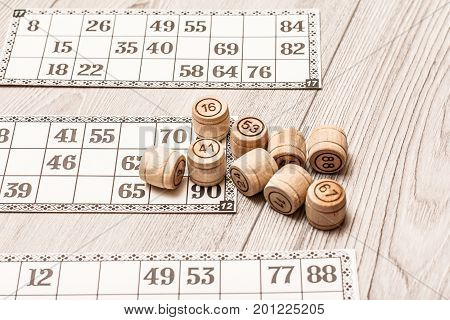 Board Game Lotto On White Desk. Wooden Lotto Barrels And Game Cards