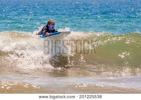 A young girl with goggles rides a wave at the beach on a boogie board. She is wearing a wet suit on a sunny day. Her mouth is open in excitement.
