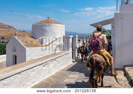 LINDOS RHODES ISLAND GREECE - JULY 9 2015: Tourists riding a donkeys past the chapel of Saint George Pahimahiotis