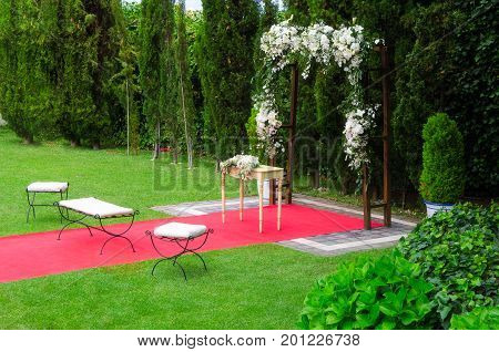 Beautiful Wedding ceremony decoration rustic altar decorated with lilies alstroemerias and chrysanths flowers behind ivy wall red carpet with whites chairs. Wedding day concept. Space for text.