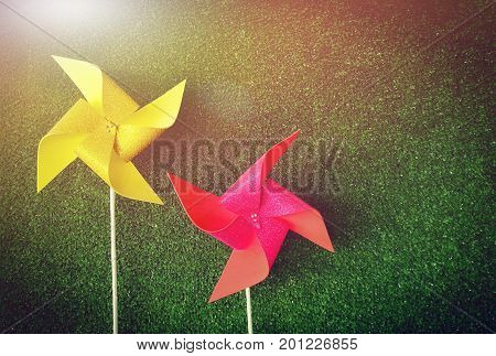Bright yellow and pink pinwheels on green grass background. Artificial light was added on the top left corner. Picture with copy space.
