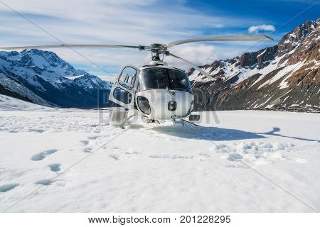 Helicopter Landing On A Snow Mountain