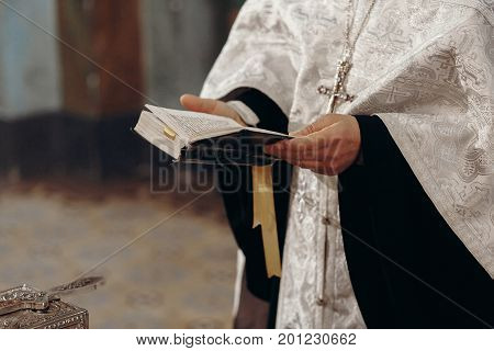 Priest reading holy bible in christian church during orthodox wedding ceremony spiritual ritual concept