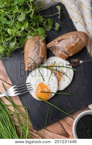Roeasted Round Eggs with Fresh Bread on Black Stone Board with Herbs