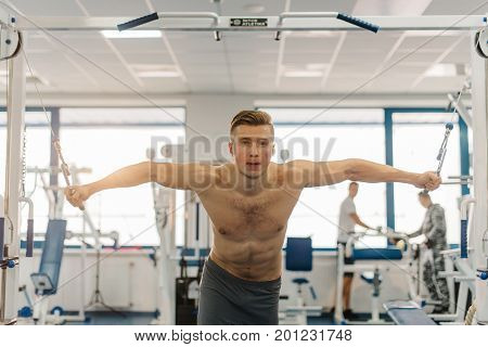 attractive man training on Fitness-station. Man with six-pack abs and strong hands. He working out to become jacked, develop strength, develop definition of muscles