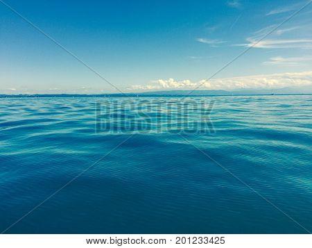 Sicht auf den Bodensee an Sommertag mit blauem Himmel, Wolken und Bergen im Hintergrund