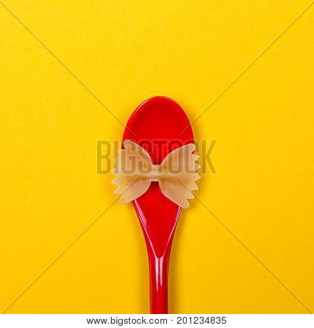 Farfalle bows pasta and red spoon on the yellow background