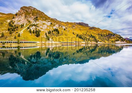 Mountain Lake Lago di Fedaia. The magic and harmony of the Dolomites. Glacial lake with cold water.  The concept of ecological and extreme tourism