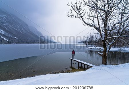 Watching the coming of a snow storm over frozen lake Bohinj in Slovenian Alps, Slovenia