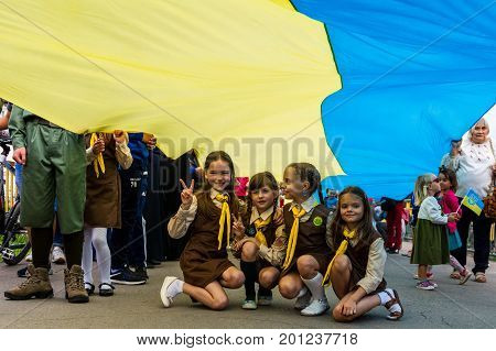 Uzhgorod Ukraine - August 23 2017: Little girls scouts sit under the 100-meter flag during the celebration of the Day of the State Flag of Ukraine in Uzhgorod.