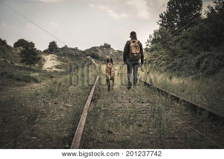 woman and her dog on old rails in the sand dune