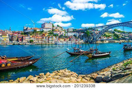 Dom Luis I bridge and traditional boats on Rio Douro river in Porto, Portugal