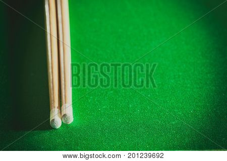 Billiards cue sticks on green table. Pool game