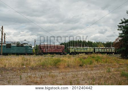 Train Lokomotive With Wagons Riding Railroad In Forest Near Village