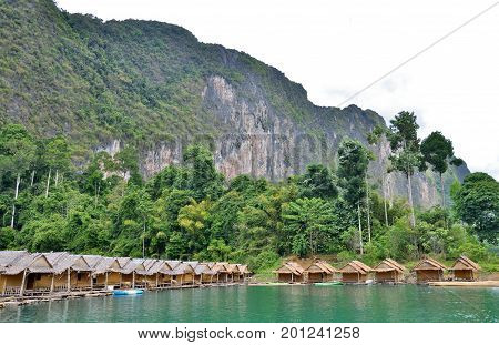 Traditional Thai bamboo house resort, floating among mountains view, clear sky and clear water in the Cheow Lan Dam (Ratchaprapa Dam) at Khao Sok National Park, Surat Thani Province, Thailand.