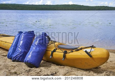 Waterproof bags standing by yellow plastic kayak on the lake shore