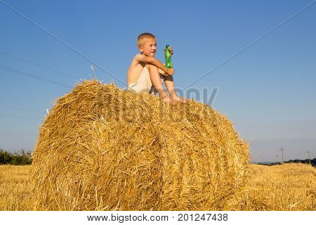 The young boy sat on a bunch of hay and held a bottle of water
