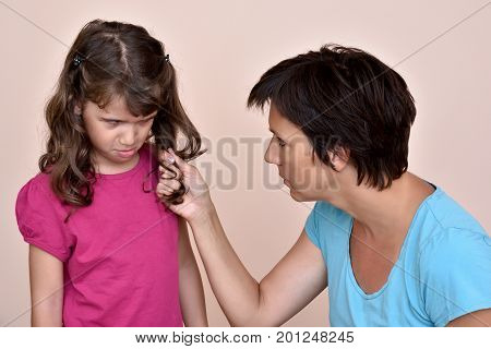Angry mother scolding and pulling the hair of the scared daughter