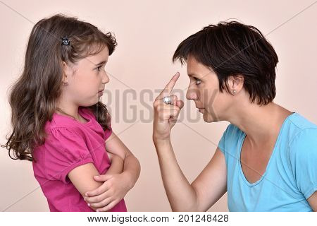 Angry mother scolding a scared cute daughter