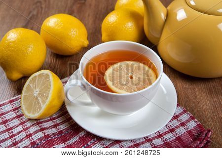 Still life of fresh lemons on a wooden table with cup of tea close up