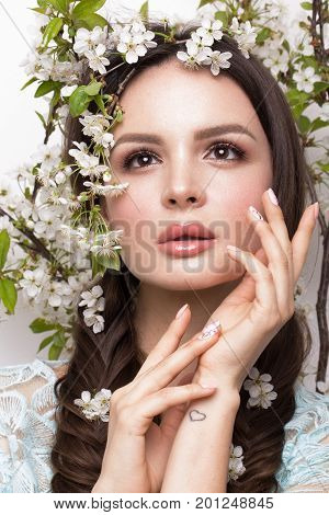 Beautiful brunette girl in blue dress with a gentle romantic make-up, pink lips and flowers. The beauty of the face. Portrait shot in the studio. poster