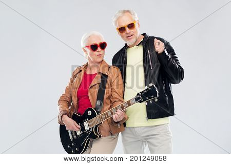 music, age and people concept - happy senior couple in sunglasses with electric guitar