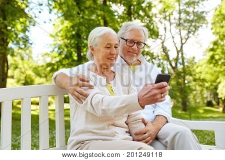 technology, relationship and old people concept - happy senior couple with smartphone taking selfie and hugging in summer