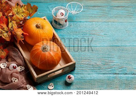 Halloween pumpkins, wooden skulls, maple leaves, eyeballs on wooden table, with space for text