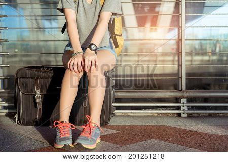 Young girl asian traveler sitting with carrying hold suitcase luggage and passenger for tour travel booking ticket flight in airport international vacation time in holiday rest and relaxation.