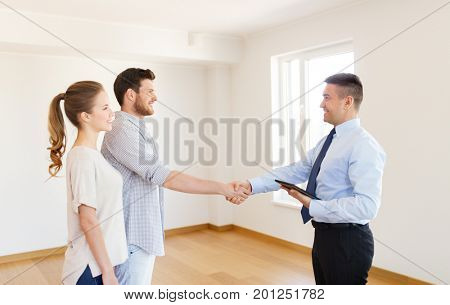 mortgage deal, people and real estate concept - happy couple and realtor with tablet pc computer shaking hands at new home