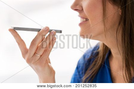 technology, communication and people concept - close up of happy woman using voice command recorder on smartphone