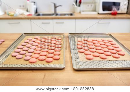 cooking, confectionery and baking concept - macarons on oven trays at bakery or pastry shop kitchen