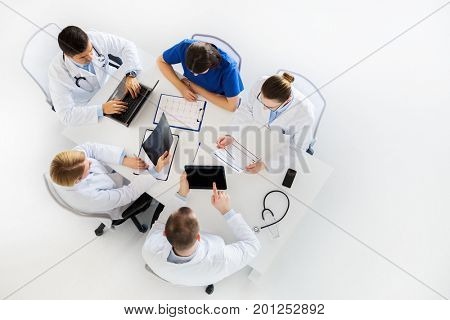 medicine, healthcare and people concept - group of doctors with x-ray, cardiogram, laptop and tablet pc computers on conference at hospital